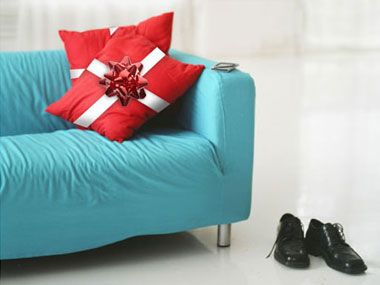 TURN PILLOWS INTO PRESENTS: Tie a bow around your throw pillows with holiday-colored ribbons, and they'll look just like Christmas gifts! Add a rhinestone pin for an extra decorating kick.