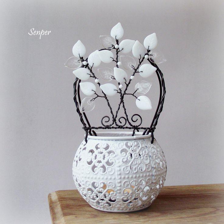 Ledové světýlko Drátovaný svícen ( stínohra ) na čajovou svíčku z černého žíhaného drátu. Základem je vyřezávaný plechový bílý svícen. Strom je zdoben skleněnými korálky v bílébarvě a skleněnými lístkyv bílé a čiré barvě. Rozměry : výška cca 19 cm ( měřeno s přesahem lístků ), výška svícnucca 7,5 cm.Šířka ucha se stromem je cca 9cm. ...