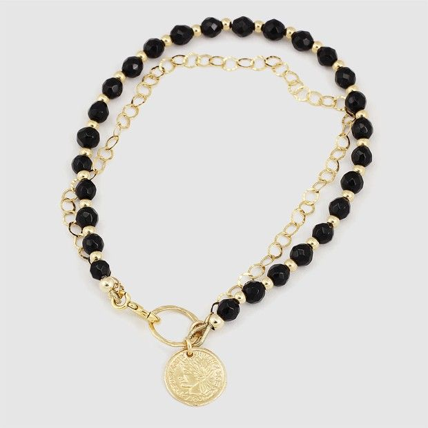A Black Onyx Bracelet with 24k gold plated goldfilled elements. the stones and beads are threaded on a heavy duty steel wire covered in nylon.