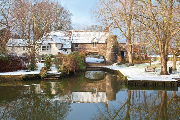 The fifteenth century flint archway at Pulls Ferry marks the start of an ancient canal built by the monks to ferry stone for building Norwich Cathedral. Here Pulls Ferry is reflected in the waters of the River Wensum on a snowy Norwich morning. Norfolk in Winter by Chris Herring.