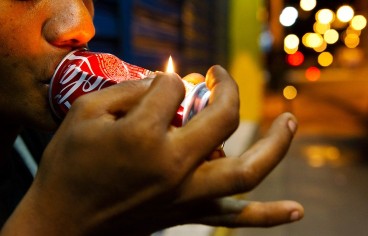 """A 23-year-old man smokes crack in downtown Manaus, on March 19, 2012. Many Brazilian cities now have their own """"cracklands,"""" areas of the city where swarms of crack users have converted entire neighborhoods into nocturnal encampments doubling as open-air crack markets. At nightfall throngs of stupefied buyers crowd around dealers before skulking away behind the telltale glow of cigarette lighters. Sociologists, health experts, and law enforcement officials all agree that crack use is a…"""