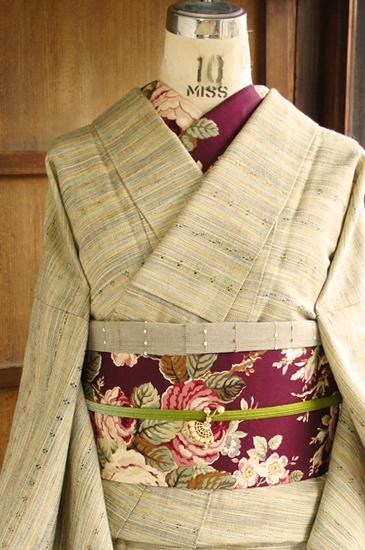 ベージュ地にパステルブルーやラベンダー、などの綺麗色の糸が織りまぜられ、色鉛筆で描いたような愛らしいストライプがふわりと浮かび上がるナチュラル・キュートなウールの単着物です。