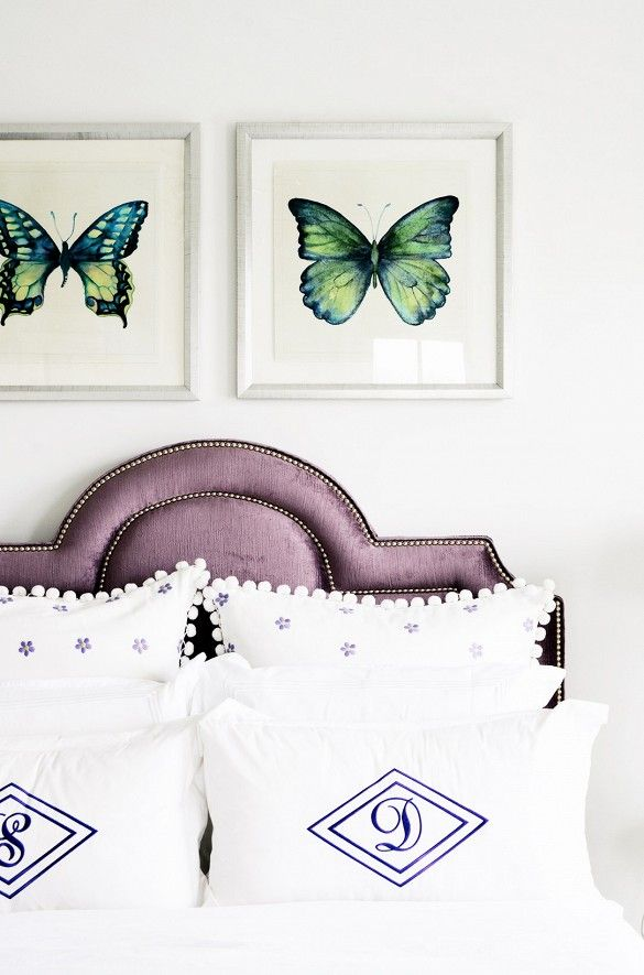 Bedroom with velvet headboard, butterfly art, and monogrammed pillows.
