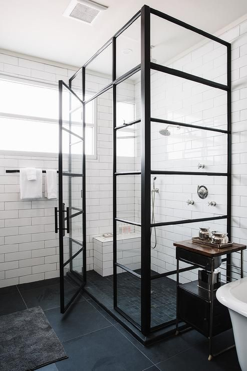 Industrial bathroom features a corner glass and shower enclosure filled with long white stacked tiles lined with small shower bench over a black…