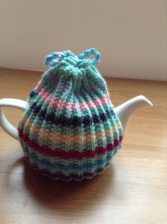 Would anyone like a cuppa?? This is what the well-dressed tea pot is wearing this season and is perfect for anyone who likes their tea! Hand knitted in a mint green colour with multi coloured stripes and a multi coloured bow at the top, this tea cosy is sure to brighten up the breakfast table. Wouldnt it make a lovely gift for a neighbor, teacher or friend, maybe someone who has helped you through tricky times, especially now that vintage style afternoon tea is so popular. It will fit a…