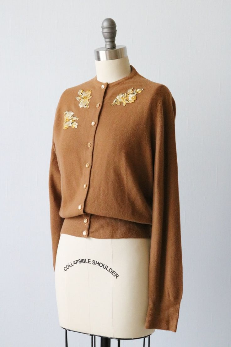 Vintage jaren 1950 zacht bruin kasjmier vest trui met een ronde hals, knoppen onderaan de voorkant en zijden draad steeg appliques in crème en goudgeel.  ---M E EEN S U R E M E N T S---  Past als een kleine tot middelgrote Bust: 37 Lengte: 21.5 Schouder: 14 Mouw: 23 Label/tijdperk: Volledige ouderwetse geïmporteerde Cashmere / jaren 1950 Stof: 100% kasjmier / jaren 1950 Vintage conditie: uitstekend  ★ Winkel meer truien en jassen hier: http://www.etsy.com/shop&#...