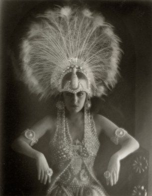 American actress Gloria Swanson, wearing an elaborate feathered headdress.