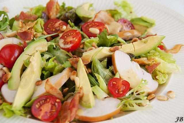 : Salade van gerookte kipfilet en avocado met mosterd-honing dresssing Ingrediënten voor 2 personen: - 1 zak gemengde sla - trostomaatjes - 6 plakjes ontspijtspek, uitgebakken - 1 avocado, in plakjes - 1 gerookte kipfilet, in plakjes - 2 el pijnboompitten, geroosterd Voor de dressing: - 1 el witte wijnazijn - 3 el extra vergine olijfolie - 1 tl mosterd - t tl honing