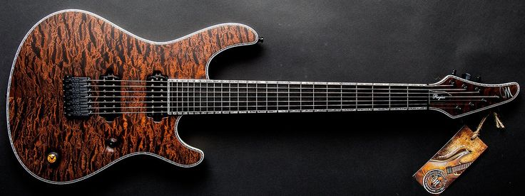 Mayones Regius 7 Custom Transparent dirty brown matte 5A Quilted Maple top 11 piece Mahogany neck with Padauk/Wenge/Maple stripes Ebony fretboard White Limba Korina body chambered Schaller Hannes bridge Luminlay side dots Stainless Steel extra jumbo frets White binding with pearloid filler 3 way toggle Wenge volume knob w Amber top is push pull for coil split Special placement of volume knob w no tone knob Hipshot Griplock locking tuners Bare Knuckle Aftermath bridge/VHII neck Pickups