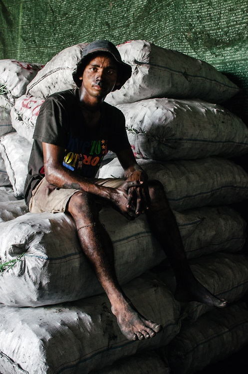 A barefoot factory worker takes a rest between packaging coal in Yangon port, Myanmar.