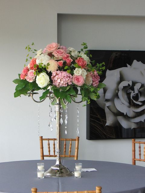 A Center Piece Of Roses And Hydrangea Sitting Atop Candelabra Centerpiece Wedding