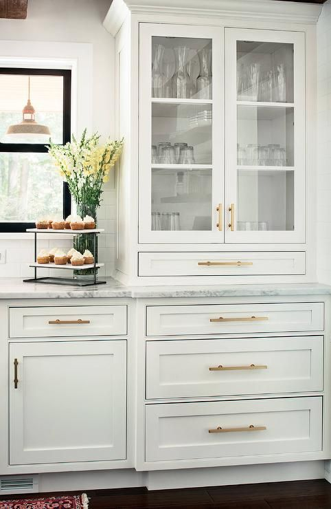 A glass front china cabinet accented with brass pulls is positioned beside black framed windows and above white shaker cabinets fitted with brass hardware and a white quartzite countertop.