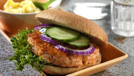 Slik gjør du: 1. Finhakk laksefilet med en skarp kniv, eller skjær den i terninger og kjør dem raskt sammen i hurtigmikseren. Bland inn salt, pepper, sitronsaft og gressløk. 2. Del deigen i fire like store deler og form fire fine burgere. 3. Stek lakseburgerne i en varm stekepanne med olje, ca. 2 minutter på hver side. 4. Legg lakseburgerne i varme hamburgerbrød sammen med salat, agurk, rødløk eller annet tilbehør du er glad i. Litt hjemmelaget aïoli smaker godt til.