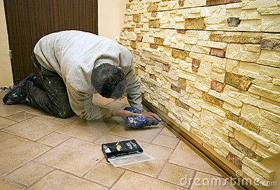 A worker drilling under new decorative tiles on the walls.   <a href='http://www.dreamstime.com/interiors-rcollection5192-resi208938' STYLE='font-size:13px; text-decoration: blink; color:#FF0000'><b>HOME BUILDING & RENOVATION »</b></a>