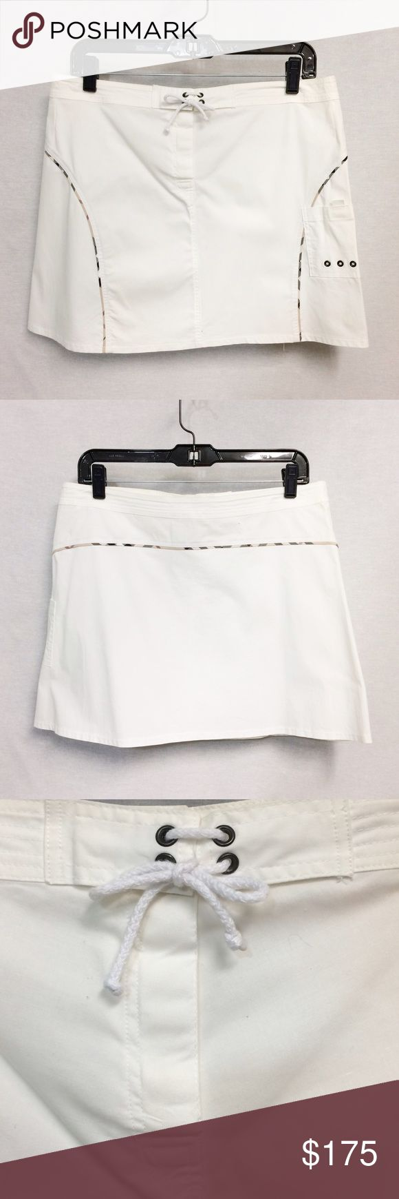 """Burberry Cargo Skirt Crisp, white, cargo skirt from Burberry! Features small cargo pocket on side, classic Burberry plaid at seams, hidden button closure, with tie-front accent. 16.5"""" waist, 15.5"""" length (when flat). Cotton with 3% spandex for stretch. Very good, used condition. Pair with flats and cotton tee for an easy spring look! Burberry Skirts"""