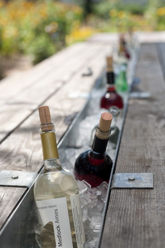Remove the middle plank of a picnic table.  Insert with a trough, and fill with ice for chilled bottles. Not for wine in my family but would be great!