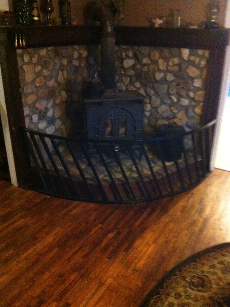 River rock wood stove surround- half an old hay ring spray painted black as  safety - Top 25+ Best Wood Stove Surround Ideas On Pinterest Wood Burning