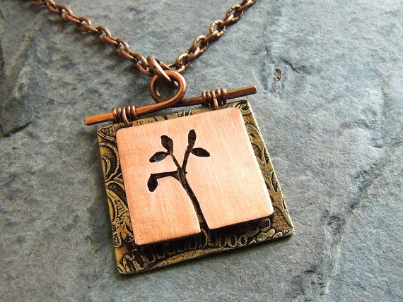 This unique pendant has a 3D effect with the top layer being raised from the bottom layer. The top layer features a copper square cut with a tree