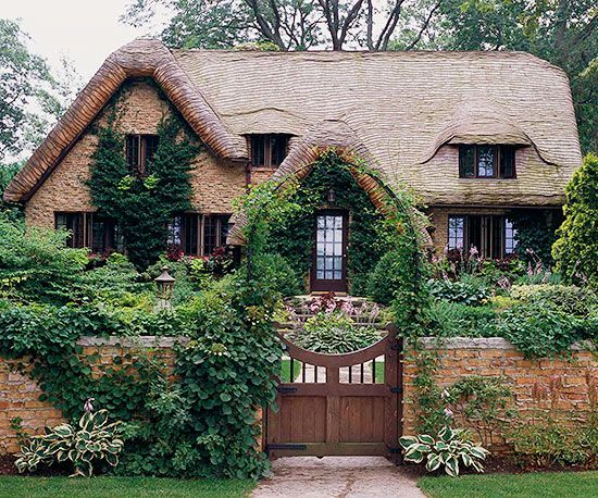 Plucked from the pages of a storybook, this quaint cottage-style home uses architecture and landscape to create a casually beautiful curb appeal. A wide wooden gate and tall stone fence both feel aged and perfectly in place, as do the naturally planted and growing collection of flowers and shrubs. A foliage-focused vine helps to soften the otherwise imposing brick facade.