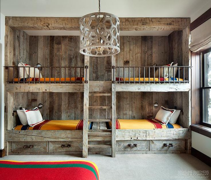 Rustic country bunk room features built-in barnwood bunk beds dressed in  yellow bedding flanking