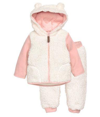 Weiß/Hellrosa. Jacke und Hose aus weichem Teddyfleece. Die Jacke hat eine Kapuze mit Jerseyfutter und angenähten Ohren, vorn einen Reißverschluss und
