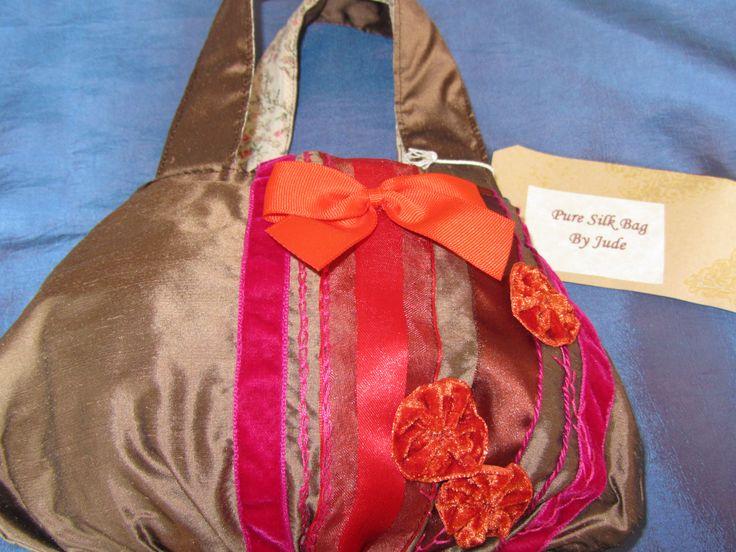 Brown silk bag with orange and pink ribbon trim.