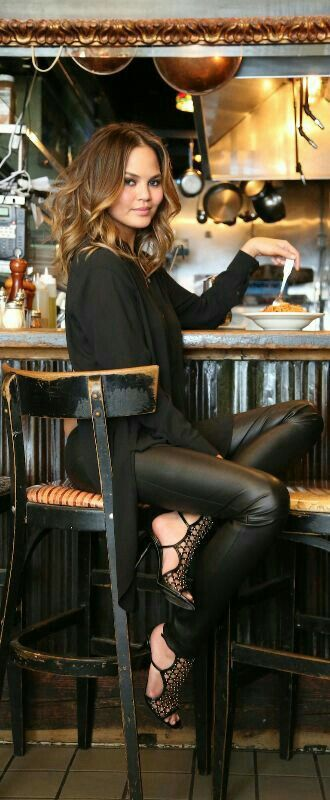 Girl seated at bar wearing leather pants