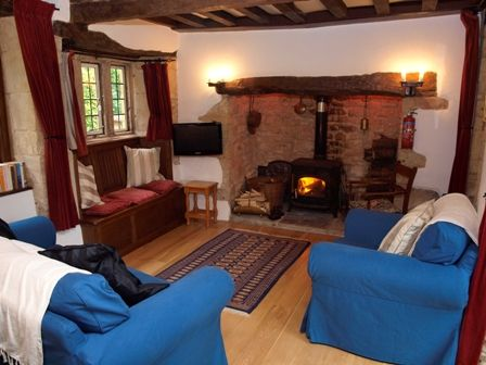 Sitting Area In Thatched Country Cottage With Woodburner Inglenook Fireplace And Carved Oak Seat