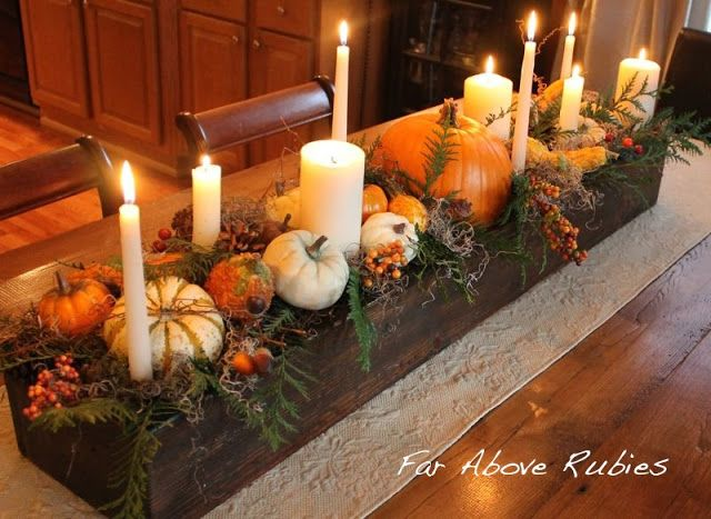 Rustic wood box filled with moss, cypress, acorns, bittersweet, pumpkins and gourds, and all sizes of ivory candles, sitting on a runner