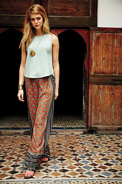 Anthropologie in Morocco, tiled wide leg pants with loose blouse, sandals, and pendant.
