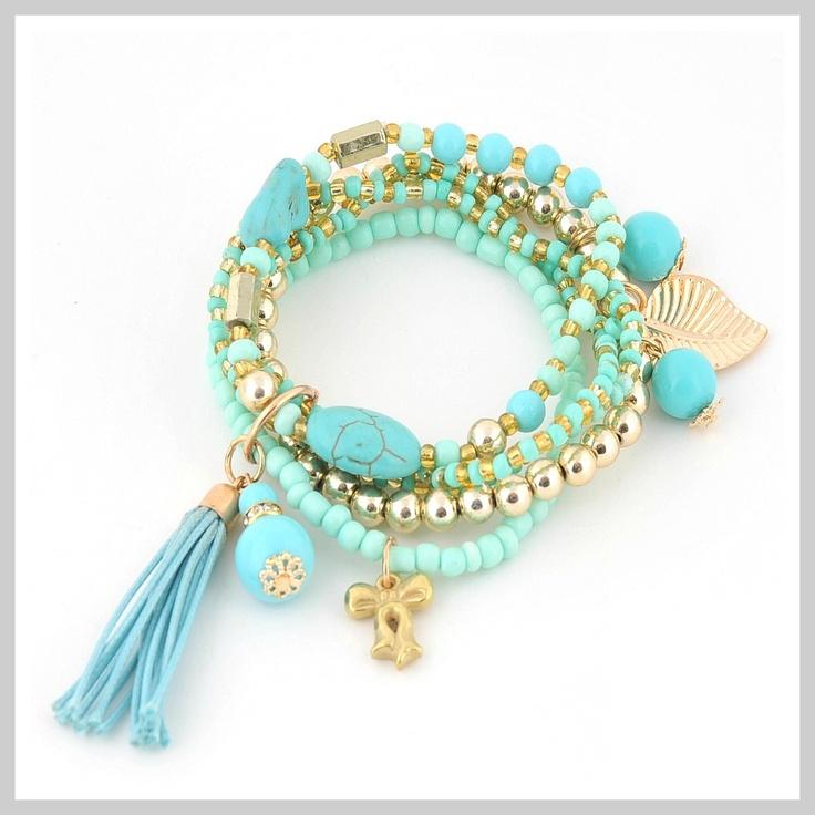 Speels zomers armbandje, bestaat uit 5 losse, rekbare armbandjes. Deze armbandjes zijn gemaakt metblauwe en goudkleurige glas-, metalen en kunstof kralen, voorzien van leukebedels en eenblauwe tassel. Alle 5 armbandje zijn rekbaar en hebben een doorsnede van 5 cm. Voor een fijne pols. Zie afbeelding.
