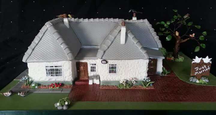 Wedding cake - exact replica of bride & grooms own house complete with various edible birds, flowers and tree