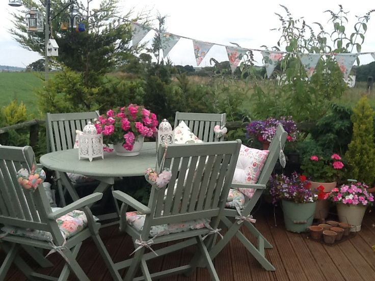 My painstakingly painted garden furniture. Cuprinol colours in Willow. Pails wombled from a second hand shop and chair pads, cushions and bunting made from a pair of curtains found in a charity shop.