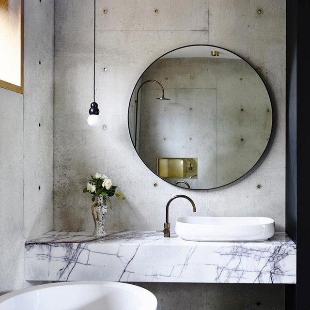 Set against an industrial backdrop, a round mirror softens the aesthetic of this minimal bathroom. We love the purposefully subtle play of the large-scale round mirror off the small round brass...