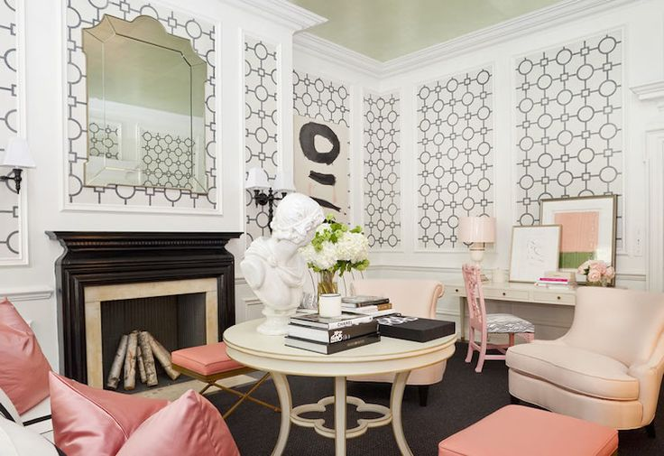 Chic pink, black and white living room features gold leafed ceilings over wainscoting clad walls which frame panels of Phillip Jeffries Union Square Wallpaper alongside a black lacquered fireplace finished with a beveled arched mirror above.