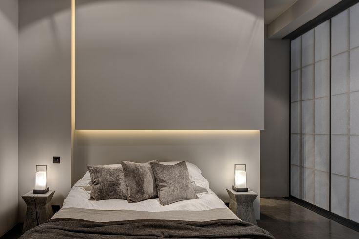 Lit walls (could be done with roofs too). Use of velvetty grey/brown furniture to soften the minimalism