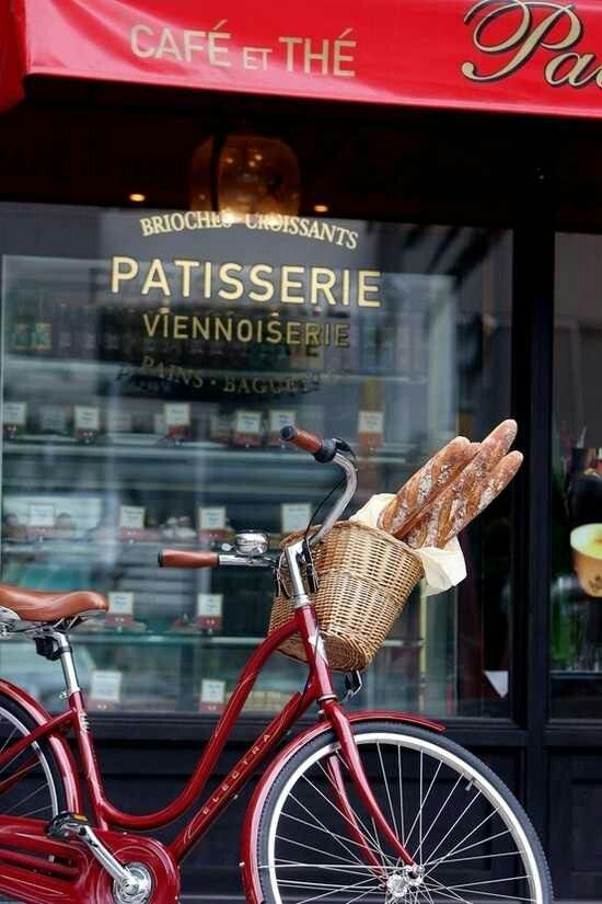 romantic French scene; red bike with baguettes & bakery in the background