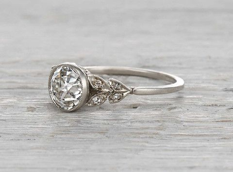 Vintage Edwardian platinum engagement ring centered with a GIA certified 1.17 carat old European cut diamond with G color and SI2 clarity. Circa 1915 Garlands of diamonds and delicate millegrain surround the bezel set center stone, making this ring a beautiful and feminine example of Edwardian design.