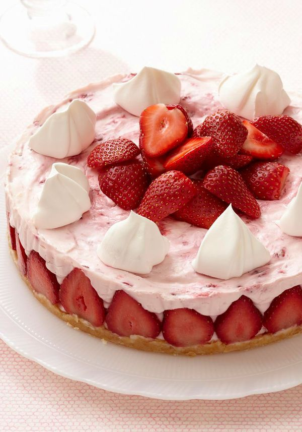Strawberry Cheesecake Supreme — Strawberries stand as sentinels around a colorful cloud of coconut-citrus cheesecake topped with more fruit and tufts of whipped cream.
