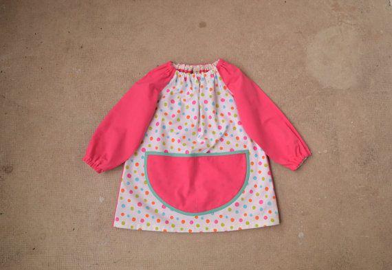 Cette magnifique Art Smock est fait de tissus de coton de 100 % ! Jai utilisé une très belle couleur Multi tissu à pois en vert, bleu, rose et Orange pour le corps de la blouse. Pour les manches raglan et le dos de la blouse, jai utilisé une toile de coton rose et encore pour la grande poche à lavant. Pour en finir avec la poche, jai utilisé un biais vert pomme, qui complimente vraiment les pois ! Il semble tellement mignon sur une paire de leggings, tout comme une petite robe ! Il sagit…