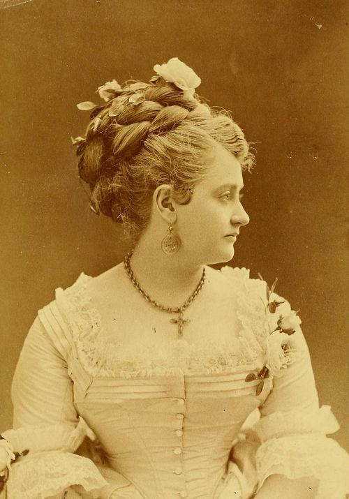 A beautiful Victorian lady wearing a large braided updo, 1874, jewelry cross necklace earrings antique x