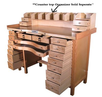Hardwood constructed jeweler's workbench with 16 spacious storage drawers and two aluminum catch trays. Pre-drilled for mounting mandrels with an aluminum slot for a bench pin and a metal work plate.