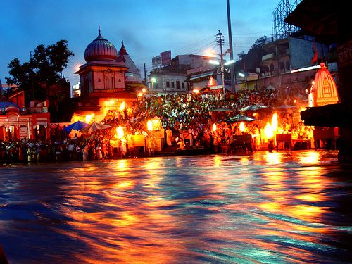 """Ganga Aarti at Har-Ki-Pauri ( हर-की-पौडी), a famous ghat at the bank of river Ganga in Haridwar, is an amazing soul touching spectacle. The golden hues of the diyas reflected in the river during the ritual is an awesome view. In literal terms, Har means """"Shiva"""" – Ki means """"Of""""-Pauri means """"Steps"""". This place is believed to be Brahmkund where drops of Amrit (elixir) fell from sky while it was being carried by Garuda, the celestial bird."""