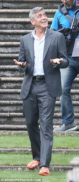 Whatever the weather: Clooney looks like he's expecting rain as he walks around the set in his unlikely footwear