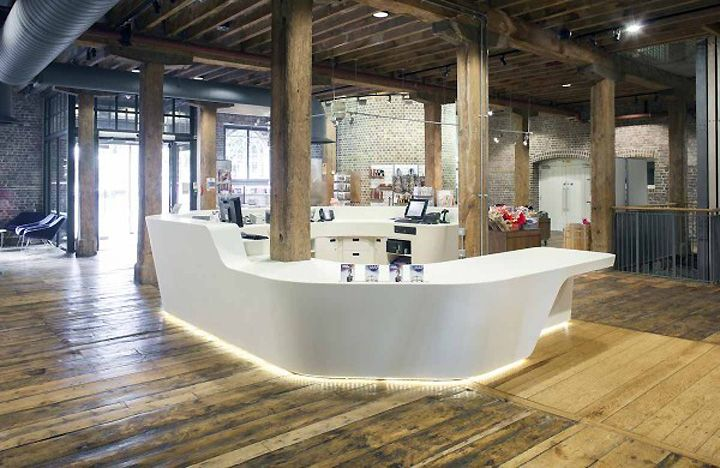 info desk design  | ... desk that wraps around to form the reception area of the building