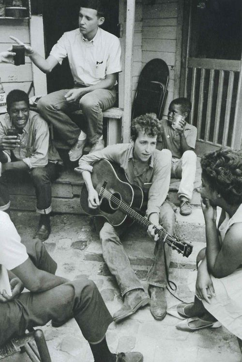 // Bob Dylan plays on the back of the SNCC office in Greenwood, Mississippi, 1963