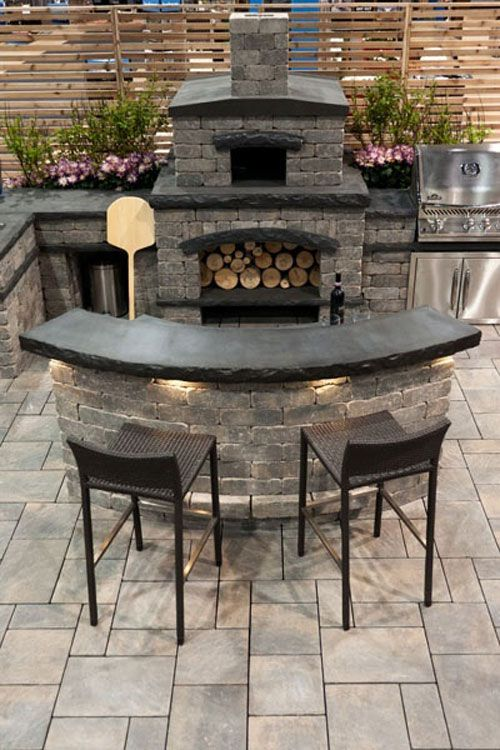 outdoor kitchen with stone oven & lighting under the island.