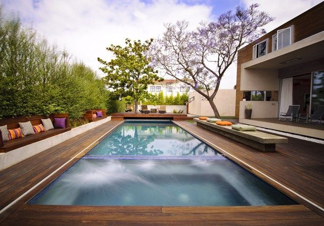 Rectangular swimming pool featuring a wood deck is perfect for this narrow backyard space.  Z Freedman Landscape Design Venice, CA