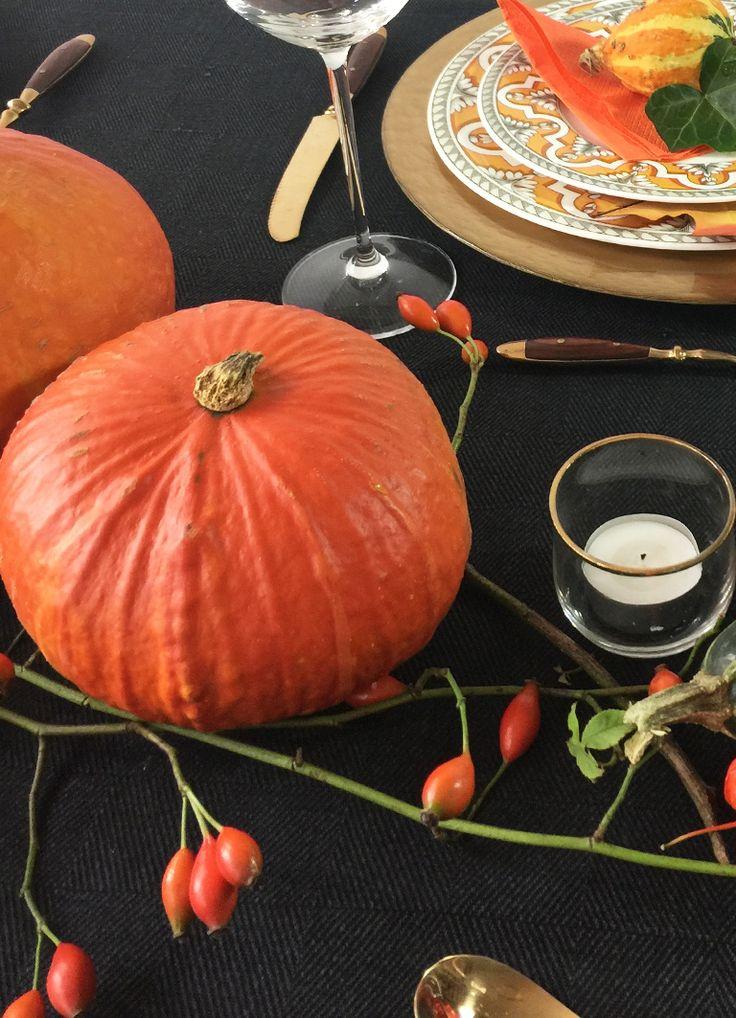 Tischdeko schwarz orange. Kürbisse und Hagebutten auf einer schwarzen Leinentischdecke.  Tablesetting black and orange with pumpkins.