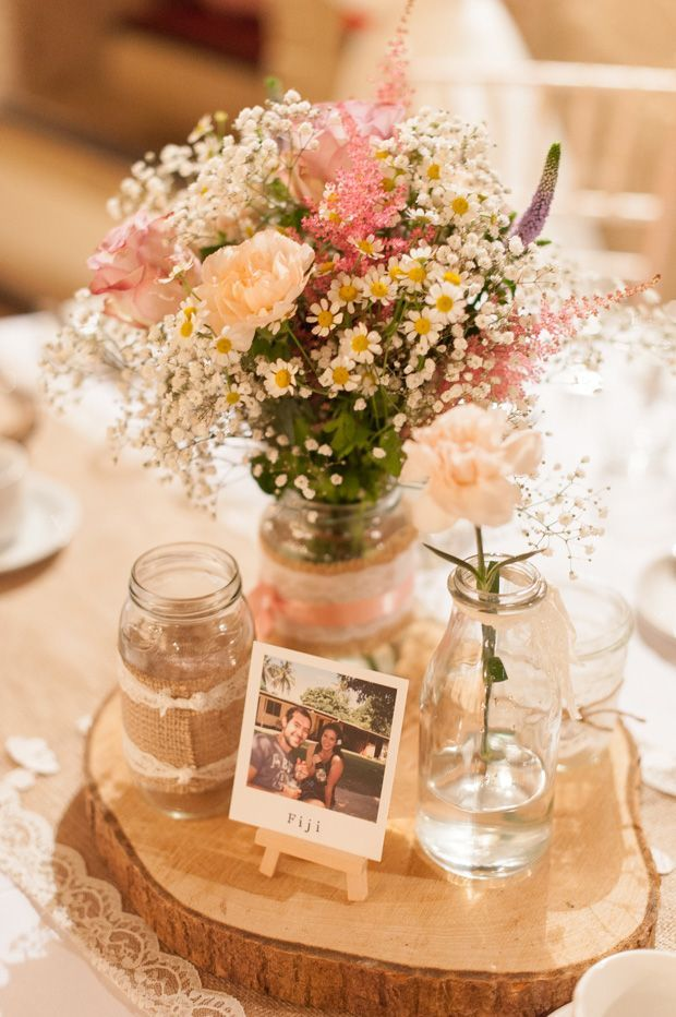 Pastel rustic table centrepieces with polaroid photos as table names | Paul and Ann's pretty barn wedding at Larchfield | www.onefabday.com